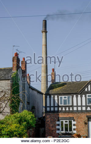 Industrial air pollution near residential area: Stanlow oil refinery chimney emitting black smoke behind houses at the village of Thornton-le-Moors, C - Stock Image