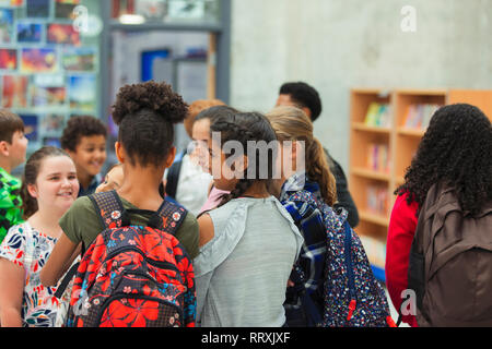 Junior high girl students talking in library - Stock Image
