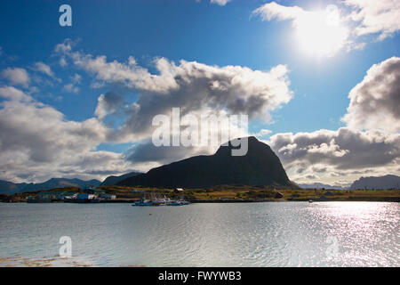 Fishing boats moored at a jetty dwarfed by a steep mountain in Hovsund on island Gimsøy on Lofoten in Norway. - Stock Image