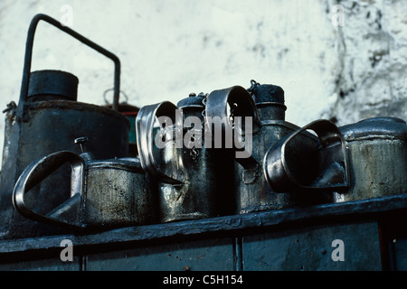 Oil cans on a shelf in an engine shed used for restoring steam engines - Stock Image