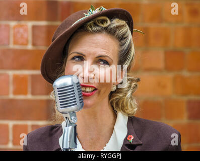 Woodhall Spa 1940s Festival - Woman in traditional 1940s dress singing - Stock Image