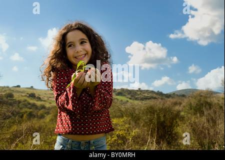 little girl holding plant outdoors - Stock Image