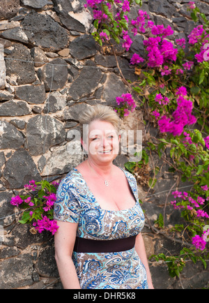 woman smiling, leaning against rock wall with bright pink flowers - Stock Image