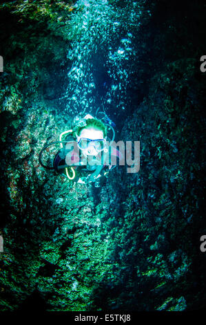Young female diver ascending through a rock chimney in the Mediterranean sea - Stock Image