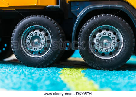 Poznan, Poland - February 9, 2019: Close up of a plastic toy construction truck standing on a carpet in soft focus. Bruder Trackmaster brand shown on  - Stock Image