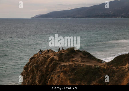Hiker Rocky beach cliffs Point Dume state park California - Stock Image