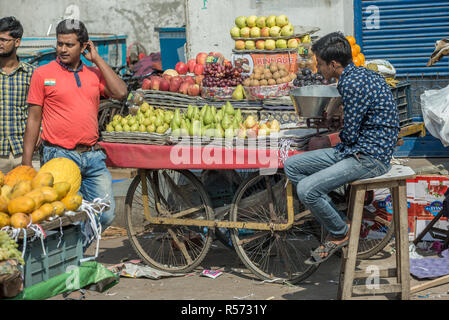 Boy on a stool selling fruits on the street, New Delhi, India - Stock Image