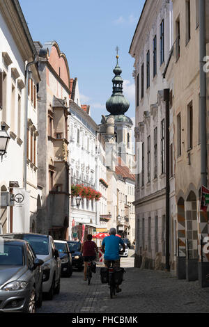 Cyclists riding along the Steiner Landstrasse in Stein old town, a popular tourist destination and UNESCO World Heritage Site in Lower Austria - Stock Image
