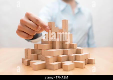 Man's hand stacking wooden blocks. Business development concept - Stock Image
