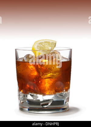 A low ball glass with bourbon over ice with a lemon wedge as garnish. - Stock Image