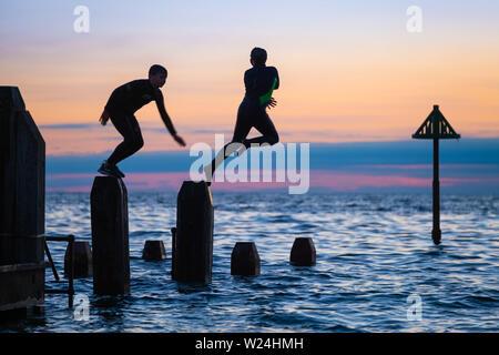 Aberystwyth Wales UK, Friday 05 July 2019  UK Weather: In the fading light at the end of a day of hot sunshine, two youngsters cool off by jumping acrobatically  into the sea off the wooden jetty in Aberystwyth on the Cardigan Bay coast, west Wales.   photo credit: Keith Morris/Alamy Live News - Stock Image