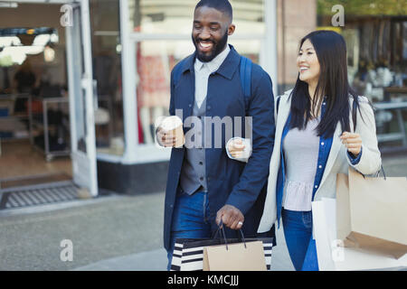 Smiling young couple walking arm in arm along storefront with coffee and shopping bags - Stock Image