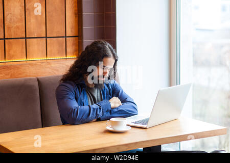 Portrait of tired handsome young adult man freelancer in casual style sitting in cafe with laptop, sleeping after hard overtime work, closed eyes buss - Stock Image