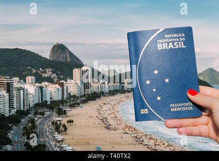 Woman holding a Brazilian passport overlooking Copacabana Beach, Rio de Janeiro, Brazil - Digital Composite - Stock Image