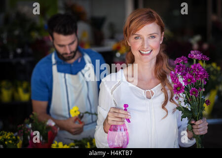 Woman holding bunch of flowers while man preparing flower bouquet - Stock Image