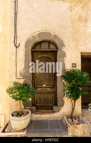 Old wooden door with potted plants in the South of France hilltop village of Gassin, Var, Cote d'Azur, France - Stock Image