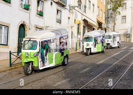 Tourists visiting Lisbon take a city tour in electric tuk tuk's. Largo Sao Martinho, Lisboa, Portugal. - Stock Image