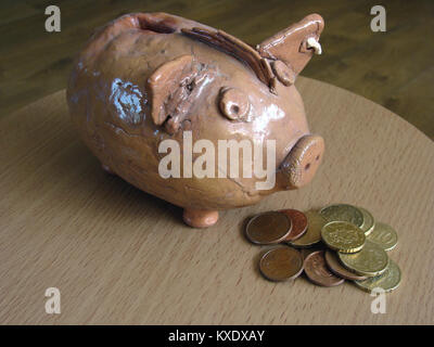 Stack of euro coins in front of piggy bank as food - Stock Image