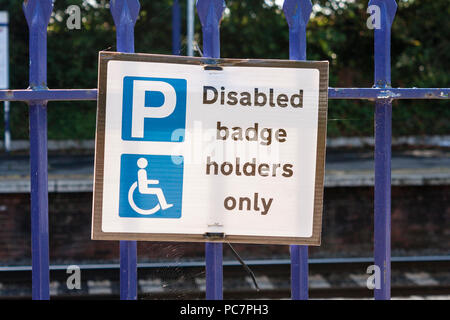 Disabled badge holders only sign on railings at UK train station - Stock Image