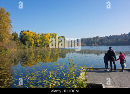 Family of three at Deer Lake park in Burnaby, British Columbia, Canada. - Stock Image