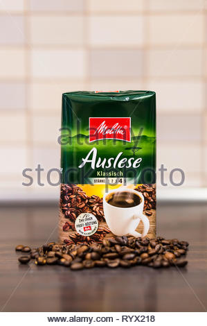 Poznan, Poland - March 12, 2019: German Melitta Auslese classic coffee in a green package and coffee beans on a wooden table in soft focus background. - Stock Image