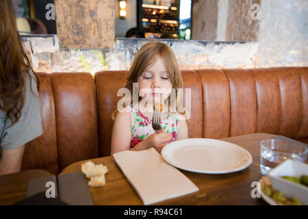 Four years age blonde girl eating and looking at croquette in fork next to woman mother sitting in brown leather sofa at restaurant - Stock Image