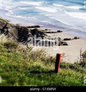 Red post on edge of public footpath along a coastal path. - Stock Image