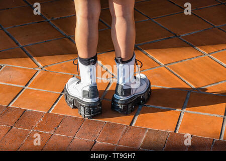 A close-up of legs and shoes of a young female adult wearing black and white high platform stylish shoes in a fashion statement standing on red tiles. - Stock Image