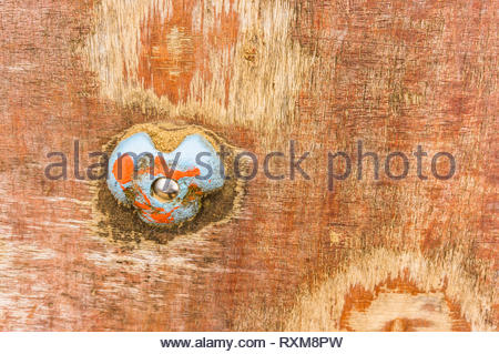 Blue hand grip with sand of a wooden climb wall. - Stock Image