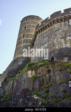 A man using a strimmer while hanging of a rope at the castle in Fougères, Brittany, France - Stock Image