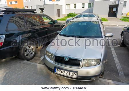 Grey Skoda car parked by a sidewalk close by - Stock Image