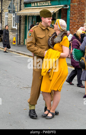 October 2018 a young man dressed as an army embraces a young lady in a yellow dress at an annual re-enactment in Pickering North Yorkshire - Stock Image