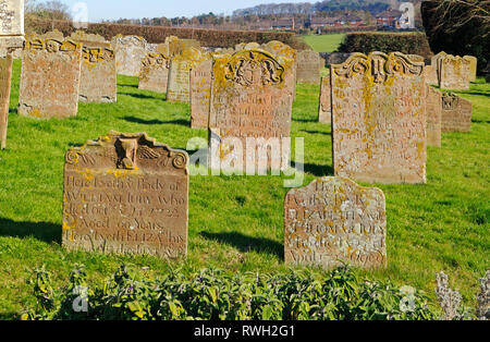 A view of mainly 18th century gravestones at the Church of St Margaret in North Norfolk at Cley-next-the-Sea, Norfolk, England, UK, Europe. - Stock Image