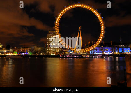 A colourful nighttime shot of the London eye - Stock Image