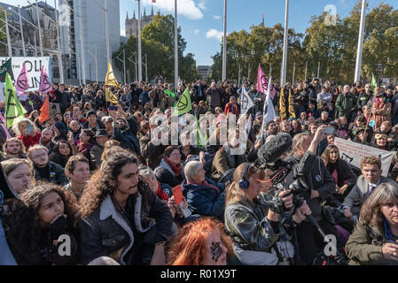 London, UK. 31st October 2018. People sit down and block the roadway in front of Parliament after making the 'Declaration of Rebellion' against the British Government for its criminal inaction in the face of climate change catastrophe and ecological collapse. They listened to speeches by George Monbiot and Green Party MP Caroline Lucas and there were songs and poems. A number of activists brought large wreaths and lay down with them, with several lock-ons. Police tried to clear the road, but the protesters ignored them, taking a show of hands to remain blocking the road for another half hour. - Stock Image