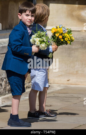 Windsor, UK. 21st April 2019. Two young boys wait to give traditional posies of flowers to the Queen as she leaves the Easter Sunday Mattins service at St George's Chapel in Windsor Castle. Credit: Mark Kerrison/Alamy Live News - Stock Image