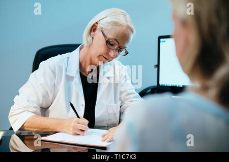 Health Care Worker Talking To Sick Senior Patient In Hospital - Stock Image