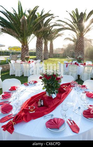 Private party table decorations by the sea at sunset - Stock Image