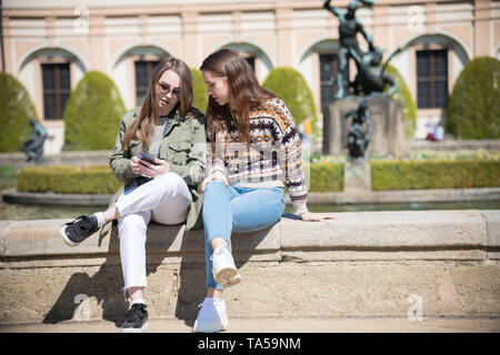 Two young women sitting near the fountain and looking at the phone. Mid shot - Stock Image