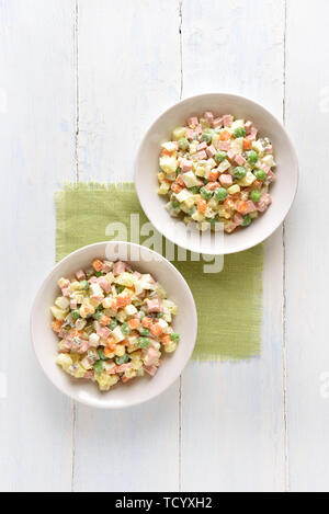Salad 'Olivier' from boiled vegetables and sausage with mayonnaise in bowl. Russian New Year or Christmas salad on light wooden background. Top view,  - Stock Image