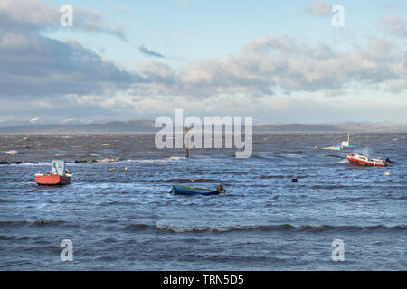 Storm Tossed Fishing Boats with the Snow Covered Hills of the Lake District Beyond, Morecambe Bay, Lancashire UK - Stock Image