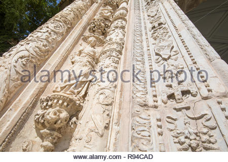 view from below of sculptures and art relief on exterior facade of ancient building of Museum Santa Cruz, landmark and monument of the Sixteenth centu - Stock Image