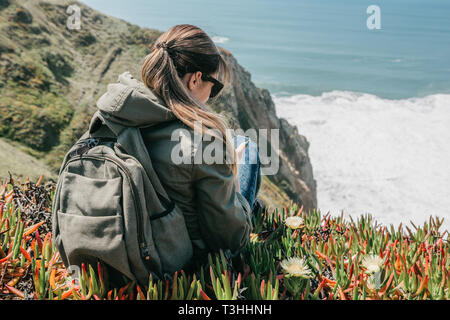 Tourist girl with a backpack uses a cell phone while sitting on the coast of the Atlantic Ocean. - Stock Image