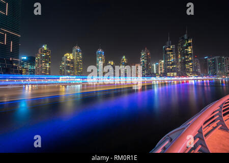 A traditional lighted Arab dhow appears as though it is moving at warp speed along the glowing waters of the Dubai Marina. - Stock Image