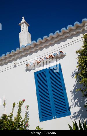 Portugal, Algarve, Carvoeiro, Shuttered Window & Chimney - Stock Image