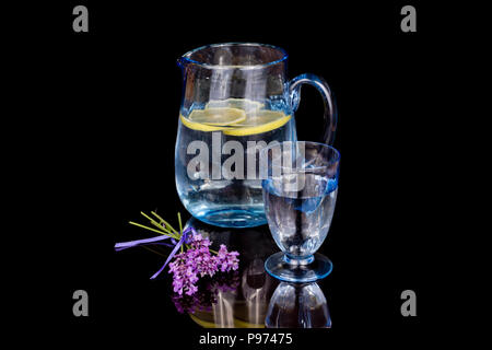 Antique blue glass water jug and glass, on a black background. - Stock Image