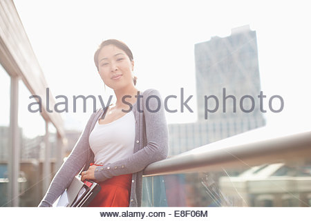 Smiling businesswoman holding folders and leaning on railing of urban balcony - Stock Image