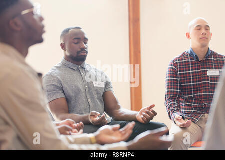 Men praying with eyes closed in prayer group - Stock Image
