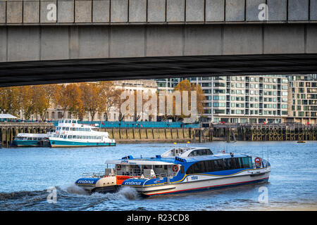 LONDON - NOVEMBER 13 : A city cruises tour sails on the Thames River sightseeing boat goes under the bridge on 13 November 2018 in London, England UK - Stock Image