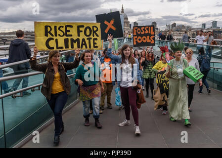 London, UK. 8th September 2018. Climate Reality supporters walk onto the Millennium Bridge for a photo at the end of their rally in front of Tate Modern, one of thousands around the world demanding urgent action by government leaders to leaders commit to a fossil free world that works for all of us.  community leaders, or Credit: Peter Marshall/Alamy Live News - Stock Image